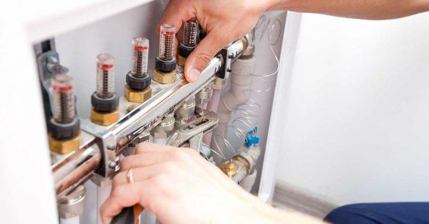 Engineer Fixing Underfloor Heating Manifold